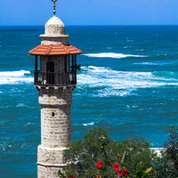 The minaret of the mosque in old Jaffa   on blue sky and  Mediterranean sea background